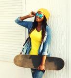 Forme a la mujer africana joven con el monopatín en ropa y gafas de sol coloridas Imagen de archivo libre de regalías