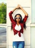 Forme a la mujer africana joven hermosa que lleva una camisa a cuadros roja y las gafas de sol en la ciudad Fotografía de archivo libre de regalías