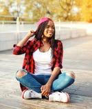 Forme a la mujer africana joven que se divierte en el parque de la ciudad, llevando una sentada a cuadros roja del casquillo de l Fotografía de archivo libre de regalías