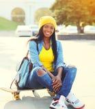 Forme a la mujer africana joven sonriente feliz con el monopatín en ciudad Foto de archivo