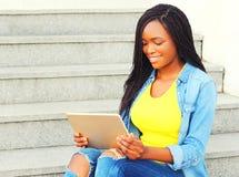 Forme a la mujer africana que usa la sentada del ordenador de la PC de la tableta Imagen de archivo