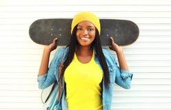 Forme a la mujer africana sonriente bastante joven con el monopatín Fotos de archivo libres de regalías