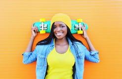 Forme a la mujer africana sonriente bastante joven con el monopatín en ropa colorida Imágenes de archivo libres de regalías