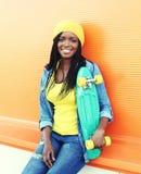 Forme a la mujer africana sonriente de los jóvenes con el monopatín en ropa colorida Imagen de archivo libre de regalías