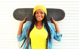 Forme a la mujer africana sonriente de los jóvenes del retrato con el monopatín en ropa colorida sobre blanco Fotografía de archivo