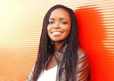 Forme a la mujer africana sonriente en ciudad sobre rojo foto de archivo libre de regalías