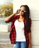Forme a la mujer africana sonriente que habla en un smartphone en la ciudad, llevando las gafas de sol a cuadros rojas de una cam Fotos de archivo