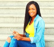 Forme a la mujer africana sonriente que usa el ordenador de la PC de la tableta Fotos de archivo