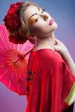 Forme a la mujer asiática que lleva el kimono rojo japonés tradicional    Foto de archivo libre de regalías