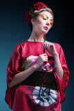 Forme a la mujer asiática que lleva el kimono rojo japonés tradicional. Gei Imagen de archivo