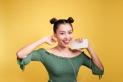 Forme a la mujer asiática sonriente que escucha la música en ove de los auriculares Foto de archivo libre de regalías