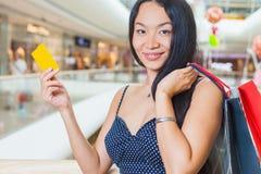 Forme a la mujer asiática que sostiene la tarjeta de crédito y los bolsos, alameda de compras Fotos de archivo libres de regalías