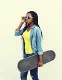 Forme a la mujer bastante africana con el monopatín en ropa y gafas de sol de los vaqueros Imagen de archivo