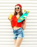 Forme a la mujer bastante fresca con el monopatín y la taza de zumo de fruta sobre blanco Imagen de archivo libre de regalías