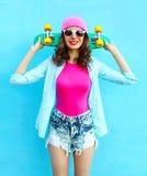 Forme a la mujer bastante fresca en estilo rosado con el monopatín Foto de archivo