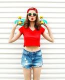 Forme a la mujer bastante fresca en gafas de sol y pantalones cortos con el monopatín sobre blanco Fotos de archivo