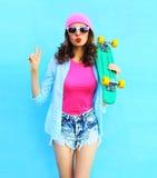 Forme a la mujer bastante fresca en ropa rosada con el monopatín sobre azul colorido Fotografía de archivo libre de regalías