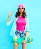 Forme a la mujer bastante fresca en rosa con el monopatín sobre azul colorido Foto de archivo libre de regalías
