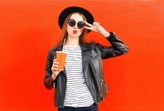 Forme a la mujer bastante joven con la taza del zumo de fruta fresca en el estilo negro de la roca que se divierte sobre rojo col Fotos de archivo