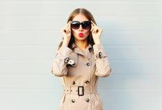 Forme a la mujer bastante joven elegante que sopla los labios rojos que llevan una capa de las lentes de sol negros sobre gris foto de archivo