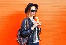 Forme a la mujer bastante joven que bebe el zumo de fruta fresca de una taza en estilo negro de la roca sobre naranja colorida Fotografía de archivo