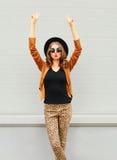 Forme a la mujer bastante joven que lleva un sombrero negro, las gafas de sol y las manos de los aumentos de la chaqueta para arr foto de archivo