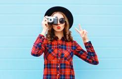 Forme a la mujer bastante joven que sopla los labios rojos con la cámara retra que lleva un sombrero negro, camisa a cuadros roja Imagen de archivo