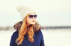 Forme a la mujer bastante rubia del retrato del invierno que lleva un sombrero de la chaqueta y las gafas de sol miran lejos sobr Imagenes de archivo