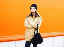 Forme a la mujer bastante rubia en ciudad sobre una naranja colorida Imágenes de archivo libres de regalías