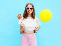 Forme a la mujer bastante sonriente con el balón y la piruleta de aire sobre azul colorido Foto de archivo