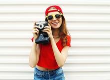 Forme a la mujer bastante sonriente con la cámara retra que se divierte sobre blanco Fotografía de archivo