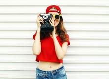 Forme a la mujer bastante sonriente con la cámara retra sobre blanco Foto de archivo