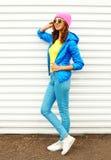 Forme a la mujer bastante sonriente en la ropa colorida que presenta sobre el fondo blanco las gafas de sol rosadas de un amarill Foto de archivo