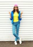 Forme a la mujer bastante sonriente en la ropa colorida que presenta sobre el fondo blanco que lleva las gafas de sol rosadas del Fotografía de archivo