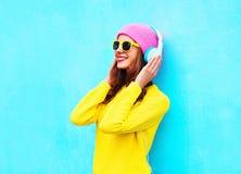 Forme a la mujer bastante sonriente que escucha la música en los auriculares que llevan el sombrero rosado colorido, las gafas de Fotos de archivo libres de regalías