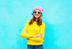 Forme a la mujer bastante sonriente que escucha la música en los auriculares que llevan un sombrero rosado colorido, gafas de sol Foto de archivo libre de regalías