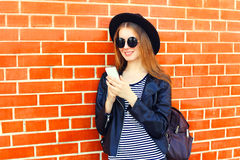 Forme a la mujer bastante sonriente que usa smartphone en estilo del negro de la roca sobre fondo de los ladrillos Fotografía de archivo libre de regalías