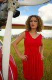 Forme a la mujer beautyful en el avión ultraligero próximo del vestido rojo Imágenes de archivo libres de regalías