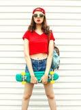 Forme a la mujer bonita con el monopatín en gafas de sol sobre blanco Foto de archivo