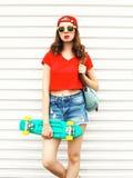 Forme a la mujer bonita con el monopatín en gafas de sol y pantalones cortos sobre blanco Fotografía de archivo libre de regalías