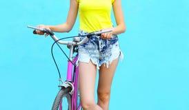 Forme a la mujer bonita con la bicicleta sobre fondo azul colorido Fotografía de archivo