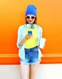Forme a la mujer bonita con la taza de café usando smartphone sobre naranja colorida Imagen de archivo libre de regalías