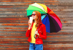 Forme a la mujer bonita con la taza de café y el paraguas colorido en día del otoño sobre el fondo de madera que lleva la chaquet Imagen de archivo