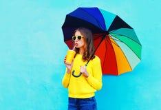 Forme a la mujer bonita con la taza del zumo de fruta fresca y el paraguas colorido en día del otoño sobre fondo azul Fotos de archivo