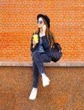Forme a la mujer bonita en el estilo negro de la roca que se sienta con la taza del zumo de fruta que habla en smartphone sobre f Imagen de archivo libre de regalías