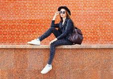 Forme a la mujer bonita en el estilo negro de la roca que se sienta en ciudad sobre ladrillos Fotos de archivo libres de regalías