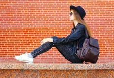 Forme a la mujer bonita en el estilo negro de la roca que se sienta sobre ladrillos Imagen de archivo