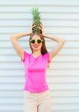 Forme a la mujer bonita en gafas de sol con la piña sobre blanco Imagen de archivo libre de regalías