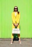 Forme a la mujer bonita en ropa amarilla del traje con la presentación del bolso Imágenes de archivo libres de regalías