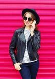 Forme a la mujer bonita que habla en smartphone en estilo del negro de la roca sobre rosa colorido Imagenes de archivo